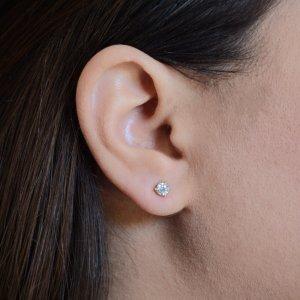Σκουλαρίκια μονόπετρα καρφωτά από χρυσό 14Κ, διακοσμημένα με λευκές πέτρες ζιργκόν. Η βάση έχει τρία στηρίγματα που περιβάλλουν στριφογυριστά την πέτρα με διάμετρο 0.5 cm.