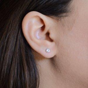 Καρφωτά σκουλαρίκια μονόπετρα από λευκό χρυσό 14Κ, διακοσμημένα με πέτρες ζιργκόν. Η βάση έχει τρία στηρίγματα που περιβάλλουν στριφογυριστά την πέτρα με διάμετρο 0.5 cm.