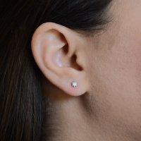 Λευκόχρυσα γυναικεία σκουλαρίκια , διακοσμημένα με λευκές πέτρες ζιργκόν. Είναι δεμένα σε εξαγωνική βάση με έξι στηρίγματα. Έχουν διάμετρο 0.35 cm.