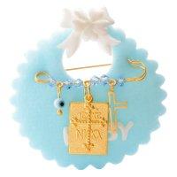 Φυλαχτό μωρού από ασήμι 925 επίχρυσο, πάνω σε γαλάζιο βελούδινο μαξιλαράκι. Είναι διακοσμημένη με ορθογώνιο κωνσταντινάτο, ματάκι, σταυρουδάκι και γαλάζιες πέτρες.