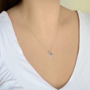 Σταυρός με ματάκι από λευκό χρυσό 14Κ. Ο μικρός σταυρός έχει λουστρέ φινίρισμα και το ματάκι είναι στρογγυλό, σε μεσαίο μέγεθος.
