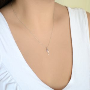 Μενταγιόν διάτρητος σταυρός με ματάκι ροζ, από λευκό χρυσό 14Κ. Ο μικρός σταυρός έχει λουστρέ φινίρισμα και το ματάκι είναι στρογγυλό, σε μεσαίο μέγεθος.