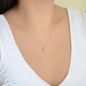 Κρεμαστό σταυρός με ματάκι ροζ, από χρυσό 14Κ. Ο μικρός σταυρός έχει λουστρέ φινίρισμα και το ματάκι είναι στρογγυλό, σε μεσαίο μέγεθος.